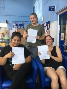 three people receiving their gcse results and smiling