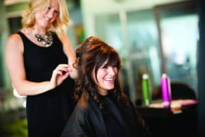 Color photo of a young woman getting her hair styled into an elegant updo in a salon.
