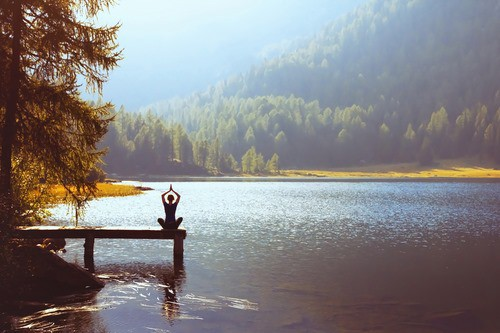 Mental Health & wellbeing - yoga by a scenic lake