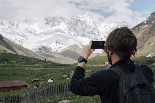 man taking photo of mountains with phone